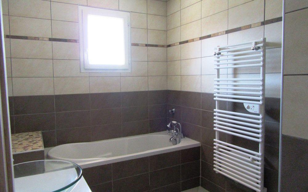 villa  de plain pied : une salle de bains  avec baignoire, douche,d'une surface d'environ- 6,76 M²